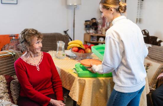 Volunteer serving a meal to senior woman in assisted living program