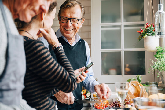 Smiling man looking at woman standing by friend in kitchen