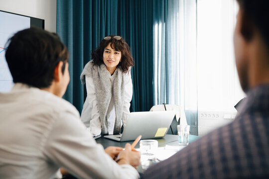 Smiling businesswoman planning strategy with male colleagues in board room during meeting