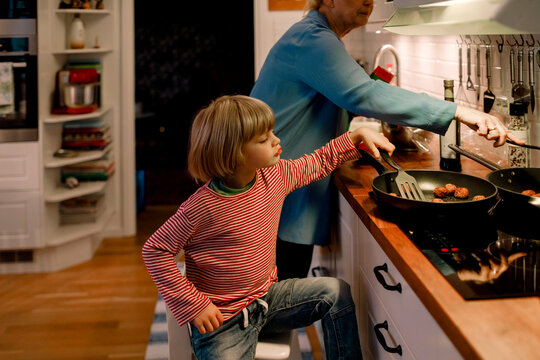 Boy helping grandmother in cooking food at home