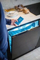 Cropped image of man using mobile app while standing by dishwasher at smart home
