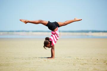 Black girl doing handstand on beach