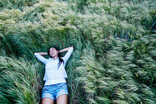 Mixed race woman laying in grass