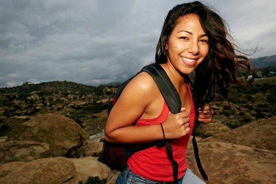 Hispanic woman smiling on rock formation