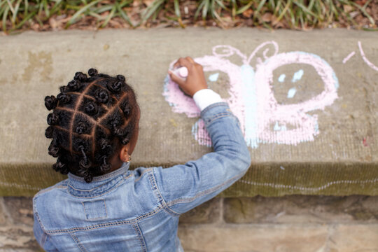 Mixed race girl drawing on cement with chalk