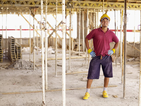 Smiling young man standing at construction site