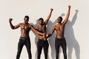 Three men raising fists in protest, standing against white wall