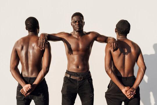 Black man leaning on friends, crossing hands behind their backs