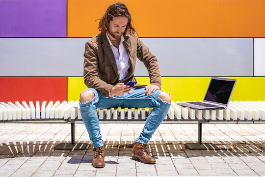 Young businessman using smart phone while sitting by laptop on bench