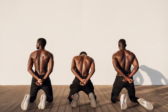 Men crossing hands behind their backs while kneeling on planks