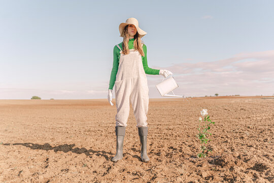 Woamn standing on barren field, watering flower