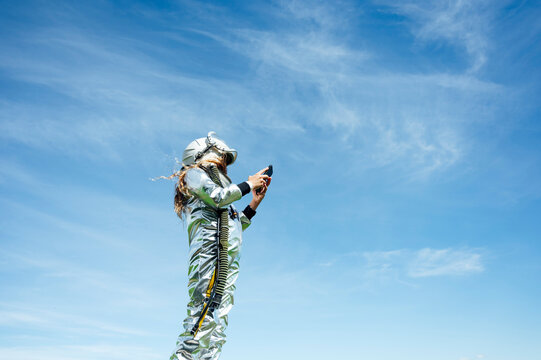 Low angle view of girl in space suit using smart phone while standing against blue sky