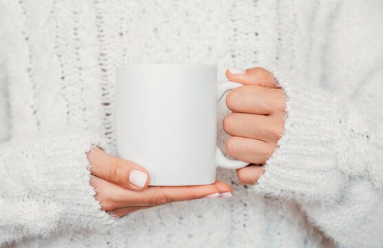 White mug mockup. Girl is holding white 11 oz ceramic cup in hands, wears cozy knitted sweater. Front view, copy space