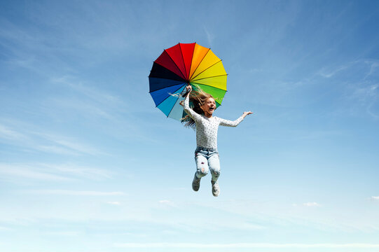 Full length of carefree girl jumping with multi colored umbrella against blue sky