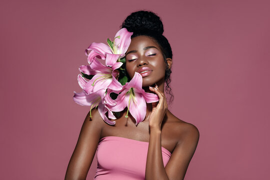Fashion beauty portrait of young African American model with pink art make up posing with lily flowers against pink background.