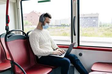 Young man wearing protective mask sitting in public bus using headphones and laptop, Spain