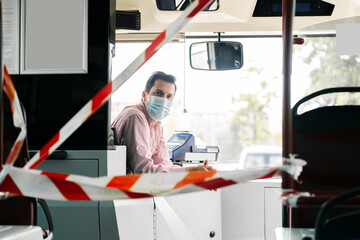 Portrait of mature bus driver wearing protective mask behind caution tape in public bus, Spain