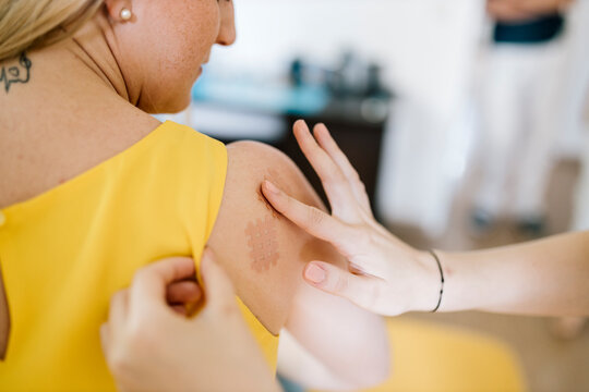 Physiotherapist applying cross tape on patient's shoulder