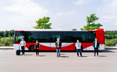 Five passengers wearing protective masks standing in a row in front of public bus, Spain