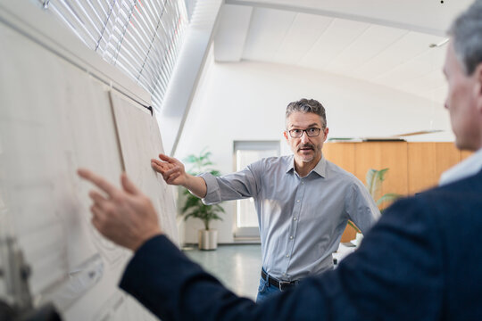 Confident mature male professional pointing while explaining strategy to businessman at office during meeting