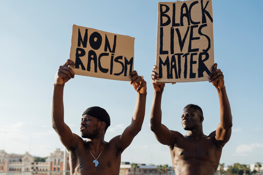 Two men holding Black Lives Matter and ati racism signs in the street