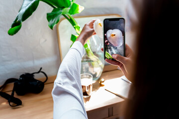 Woman photographing fresh calla lily flower in vase through smart phone at home