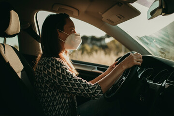 Mid adult woman with protective mask driving car