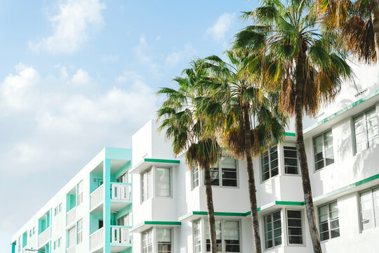Art deco buildings and palm trees against sky during sunny day, Florida, USA