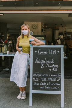 Cafe owner with face mask standing by menu board with Corona special offers