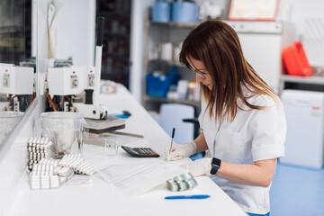 Confident female scientist writing data at desk in laboratory