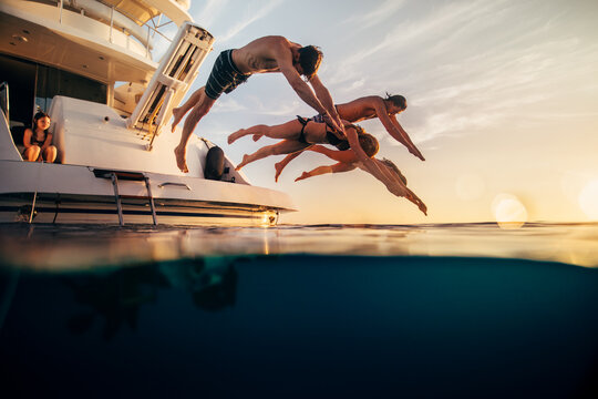Men and women diving into sea while girl sitting in yacht during sunset