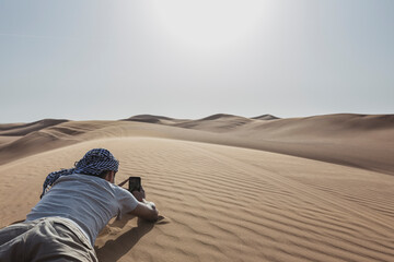 Male tourist taking picture through smart phone while lying on sand dune at desert in Dubai, United Arab Emirates