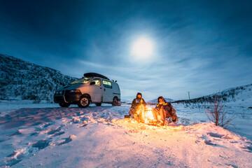 Campers at camp fire in winter landscape in polar night, Kilpisjaervi, Enontekioe, Finland