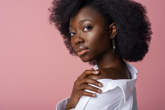 Elegant beautiful African American woman wearing classic white shirt, looking at camera, posing in studio, on pink background. Close up portrait. Copy, empty space for text