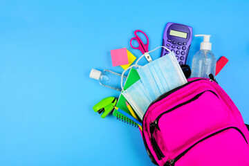 Backpack full of school supplies and COVID 19 prevention items. Top view, spilling onto a blue...