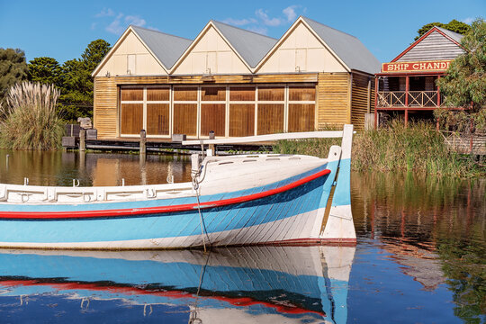 WARRNAMBOOL, VICTORIA, AUSTRALIA - JANUARY 2020: Flagstaff Hill Maritime Museum, village marina with ship chandler and boat floating in foreground