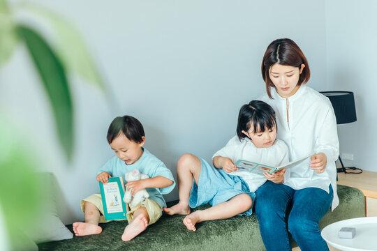 白くて明るいリビングで親子が本を読んでいる family book