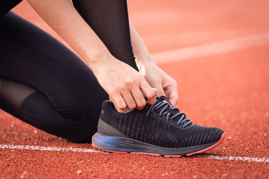 Close up of a woman athelete runner ties shoelace before jogging workout in the city stadium. Healthy and rereation stock photo.