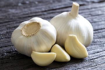 Raw Garlic Bulb and Cloves on dark wooden background