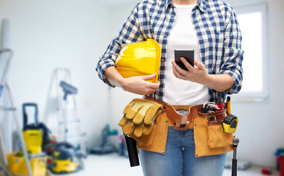 repair, construction and building concept - close up of woman or builder with smartphone, helmet and working tools on belt over utility room background