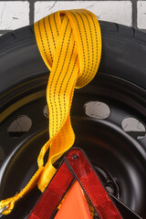 on the spare tire for the car lies a yellow tow rope and a warning triangle, close-up background