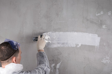 a man in special clothes conducts plastering work on the wall, back view