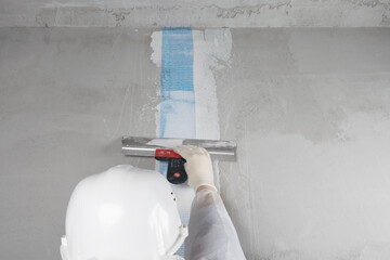 a repairman in a white helmet applies mortar with a spatula to the mesh glued to the seam on the wall, rear view, close-up