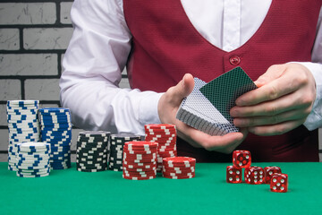 poker game concept: the croupier deals the cards, playing chips are laid out on the green cloth