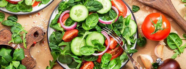 Spring vegan salad with spinach, cherry tomatoes, corn salad and red onion. Healthy food concept. Panoramic banner with copy space