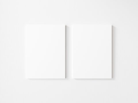 Two empty vertical canvas frame on white wall. 3d illustration.