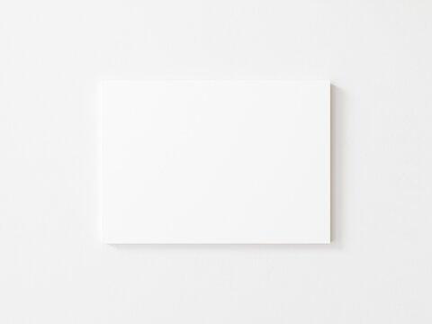 Empty horizontal canvas frame on white wall. 3d illustration.