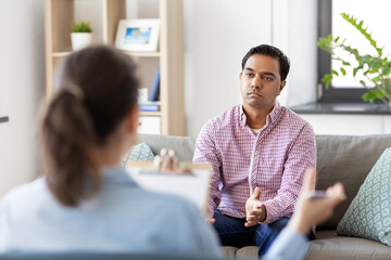 psychology, mental therapy and people concept - sad young indian man patient and woman psychologist at psychotherapy session