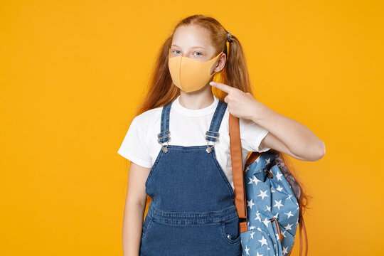Young redhead school teen kid girl 12-13 years old in white tshirt face mask backpack isolated on yellow background children studio portrait Distance education at home quarantine covid-19 ncov concept