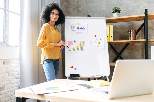 Online presentation, webinar, online meeting. A young african american woman speaks to the audience via video call, video connection. She stands near flip chart and looks at screen with online viewers